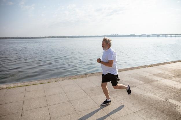 Uomo anziano come corridore con bracciale o fitness tracker in riva al fiume. modello maschio caucasico che pratica corsi di jogging e cardio nella mattina d'estate. stile di vita sano, sport, concetto di attività.