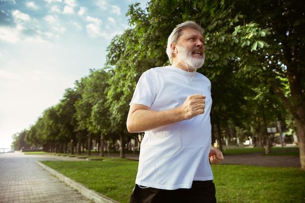 街の通りで腕章またはフィットネストラッカーを持つランナーとしての年配の男性。夏の朝にジョギングとカーディオトレーニングを練習している白人男性モデル。健康的なライフスタイル、スポーツ、活動の概念。