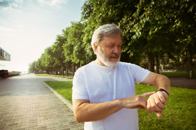 街の通りでフィットネストラッカーを持つランナーとしての年配の男性。夏の朝にジョギングや有酸素運動をしながらガジェットを使用する白人男性モデル。健康的なライフスタイル、スポーツ、活動の概念。