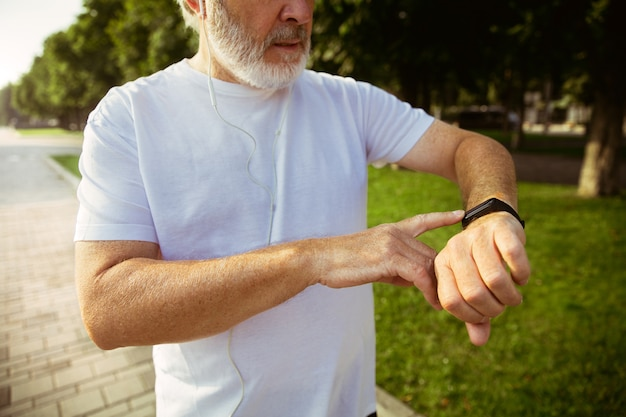 도시의 거리에서 피트니스 추적기와 주자로 수석 남자. 여름 아침에 조깅과 심장 훈련 동안 가제트를 사용하는 백인 남성 모델. 건강한 라이프 스타일, 스포츠, 활동 개념.