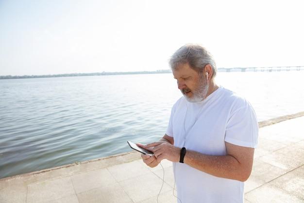 川沿いでフィットネストラッカーを持つランナーとしての年配の男性。夏の朝にジョギングや有酸素運動をしながらガジェットを使用する白人男性モデル。健康的なライフスタイル、スポーツ、活動の概念。