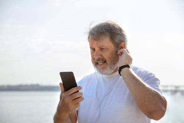 川沿いでフィットネストラッカーを持つランナーとしての年配の男性。