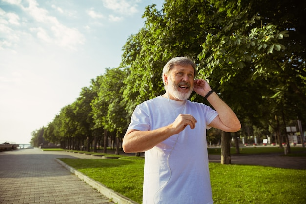 Senior man as runner with fitness tracker at the city's street. caucasian male model using gadgets while jogging and cardio training in summer's morning. healthy lifestyle, sport, activity concept.