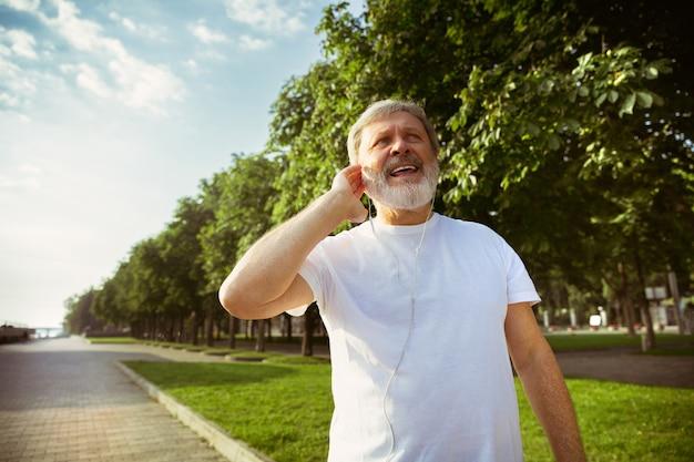 Uomo anziano come corridore con fitness tracker in strada della città. modello maschio caucasico utilizzando gadget durante il jogging e l'allenamento cardio nella mattina d'estate. stile di vita sano, sport, concetto di attività.