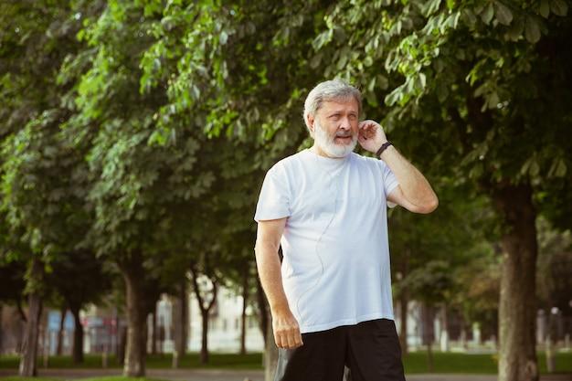 Uomo anziano come corridore con tracker di fitness in strada della città.