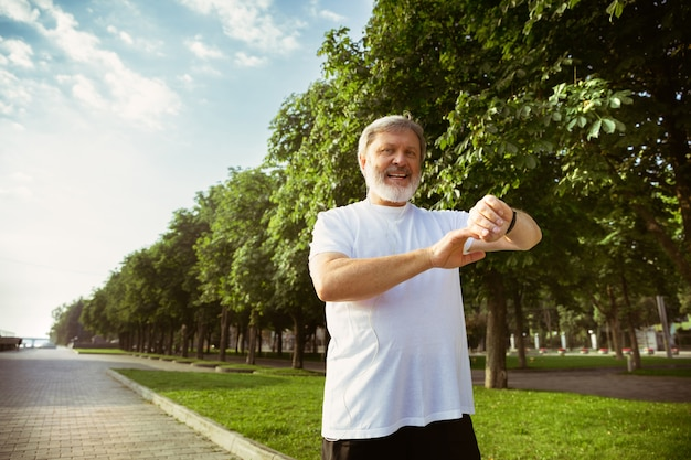 Senior man as runner with fitness tracker at the city's street