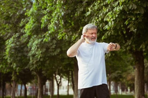 Uomo anziano come corridore con tracker di fitness in strada della città