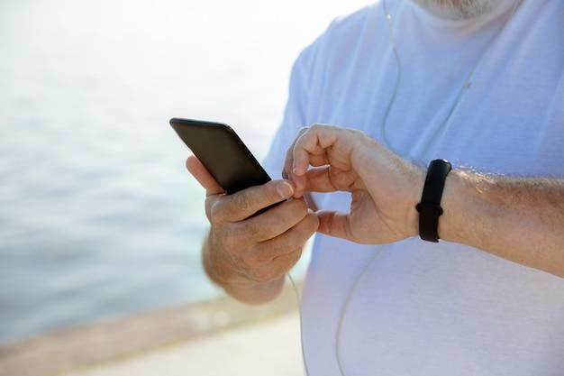 Uomo anziano come corridore con fitness tracker in riva al fiume. modello maschio caucasico utilizzando gadget durante il jogging e l'allenamento cardio nella mattina d'estate. stile di vita sano, sport, concetto di attività.