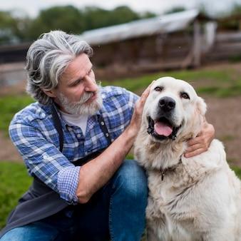 Старший мужчина на ферме с собакой