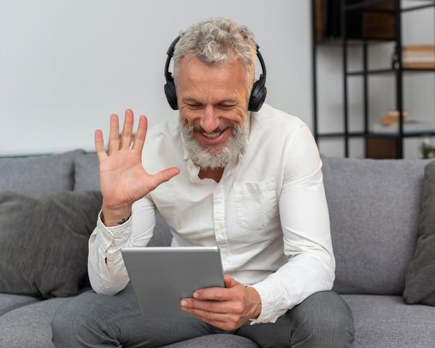 Старший мужчина дома на диване с видеозвонком на планшете и в наушниках