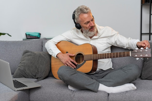 Старший мужчина дома на диване, используя ноутбук для изучения уроков игры на гитаре