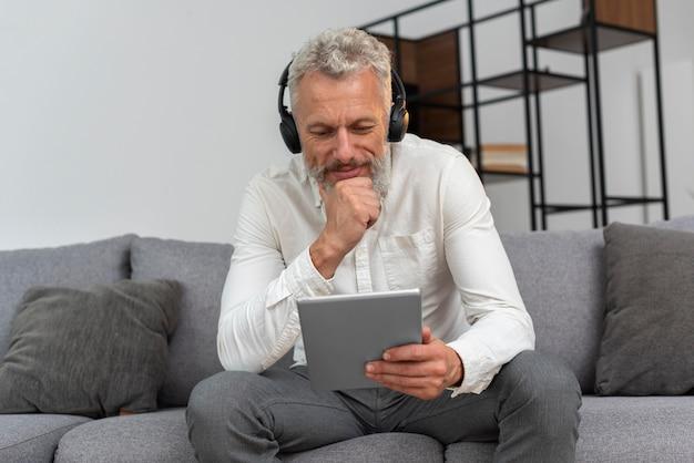 Старший мужчина дома на диване с помощью планшетного устройства и наушников