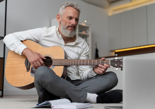 Старший мужчина дома на полу берет уроки игры на гитаре