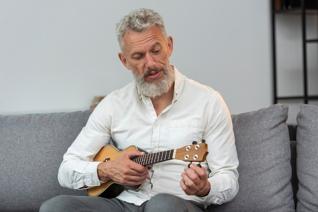 Старший мужчина дома играет на укулеле на диване