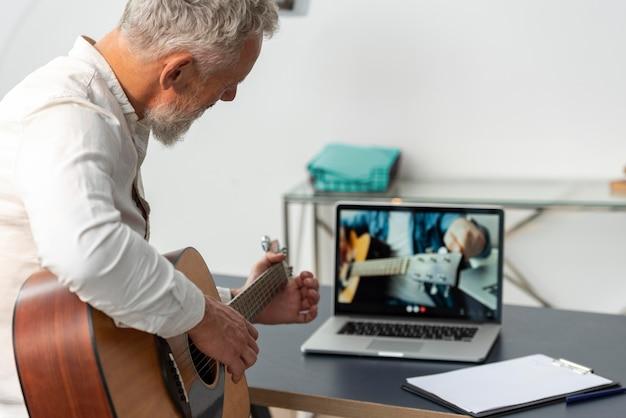 Старший мужчина дома, изучая уроки игры на гитаре на ноутбуке