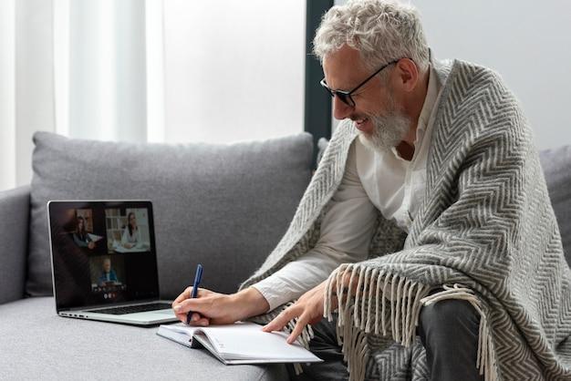 Старший мужчина дома учится на ноутбуке и делает заметки