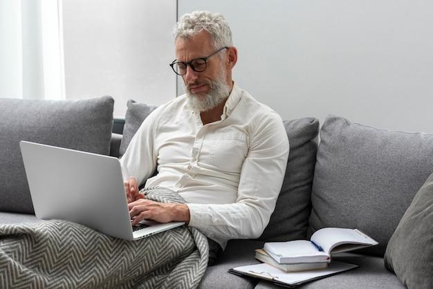 Старший мужчина дома учится на диване, используя ноутбук