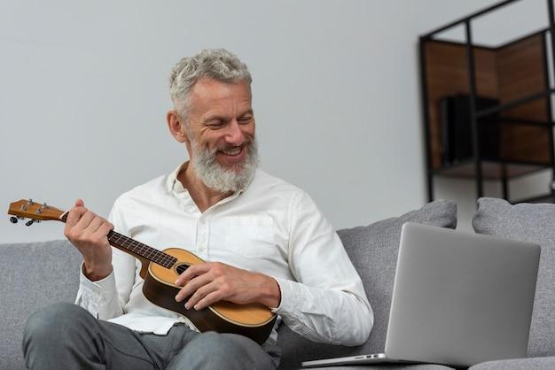 Старший мужчина дома, изучая уроки укулеле на ноутбуке