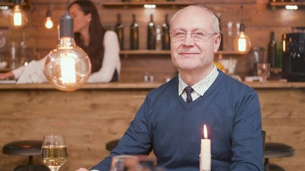 カメラに微笑んでレストランのテーブルで年配の男性。レストランの年配の男性。幸せな男。リラックスした男。