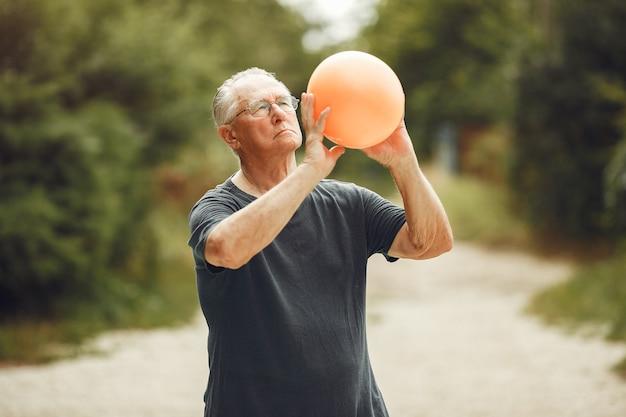 サマーパークの年配の男性。ボールを使ったおじいさん。