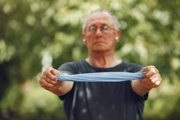 Старший мужчина в летнем парке. grangfather использует ластик.