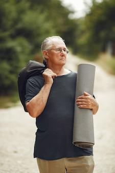 Старший мужчина в летнем парке. grangfather с циновкой.