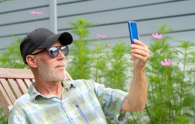 Senior man in a baseball cap portrait making selfie