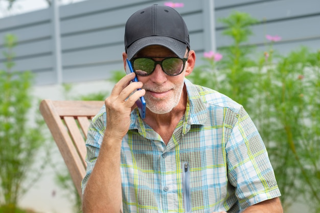 Senior man in a baseball cap portrait using smartphone