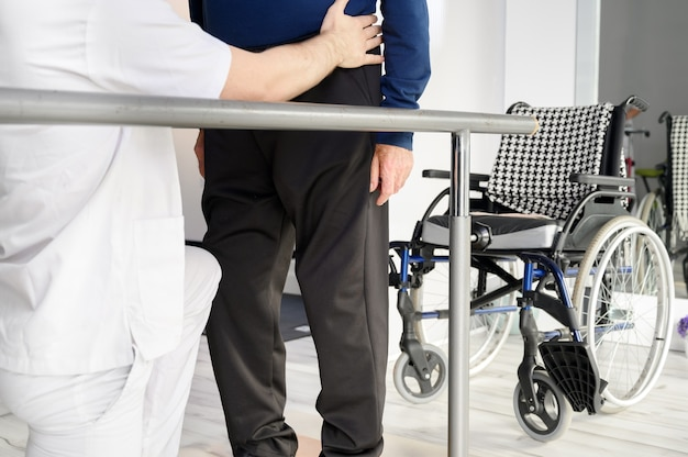 Senior man being assisted by physiotherapist in rehab center.