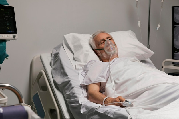 Старший мужчина дышит с помощью специального оборудования в больнице