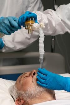 Старший мужчина дышит с помощью специального оборудования