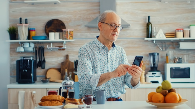 Senior man browsing on internet using smartphone in kitchen while enjoying morning coffee during breakfast. authentic portrait of retired senior enjoying modern internet online technology