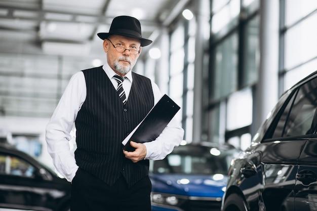 Senior man in a car showroom choosing a car