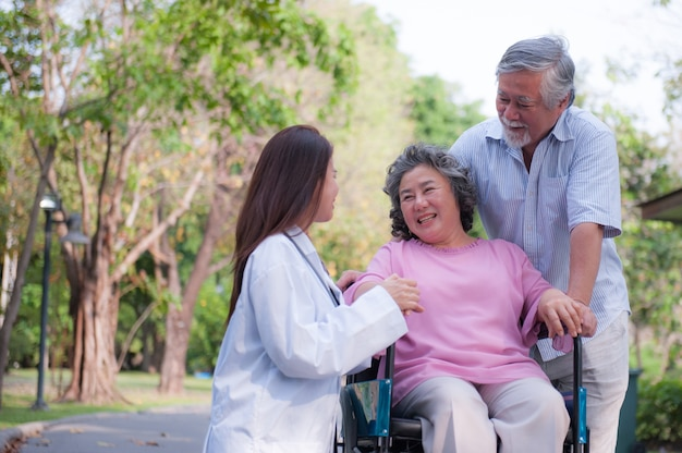 Senior man caring for disabled wife in his wheelchair with his nurse and wife in the park.