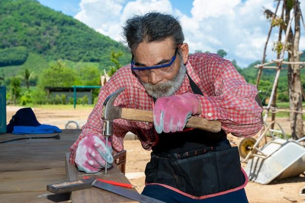 Плотник старшего человека, старый плотник работая в мастерской плотничества.