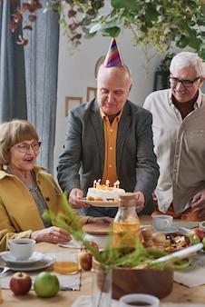 パーティーで年配の女性の誕生日を祝っている間、キャンドルでケーキを運ぶ年配の男性