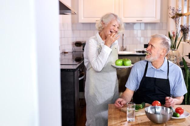 野菜を彫る年配の男性とリンゴの皿を持った妻が一緒に料理をし、健康を楽しんでいます。家に