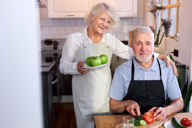 野菜を彫る年配の男性とりんごでお皿を持った妻、笑顔で一緒に料理し、健康を楽しんでください。自宅で