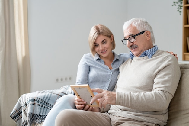 Senior man in casualwear pointing at photo in frame while discussing it with his young pretty blonde daughter at home