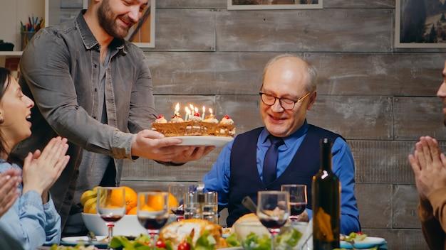가족과 함께 생일을 축하하는 노인. 맛있는 케이크. 슬로우 모션 촬영