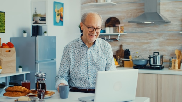 Senior man chatting and waving during a video call using laptop in kitchen holding a cup of coffee. elderly person using internet online chat technology video webcam making a video call connection cam