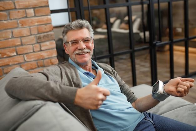 自宅のソファに横になって血圧をチェックする年配の男性。