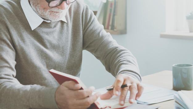 Старший человек, проверяющий свой календарь