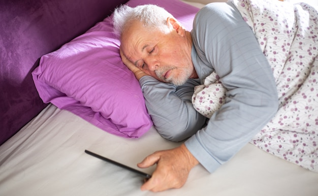 Senior man checking the news on the tablet in the bed in morning , lifestyle concept