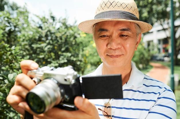 年配の男性がカメラで写真をチェック