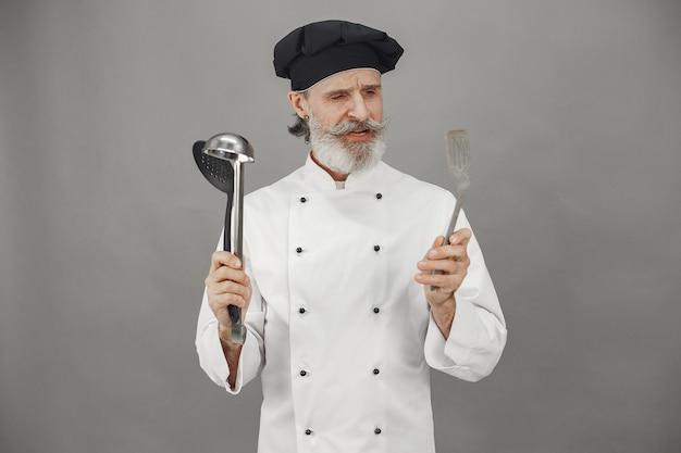 年配の男性はおたまを選びます。頭に黒い帽子をかぶったシェフ。ビジネスへの専門的なアプローチ。