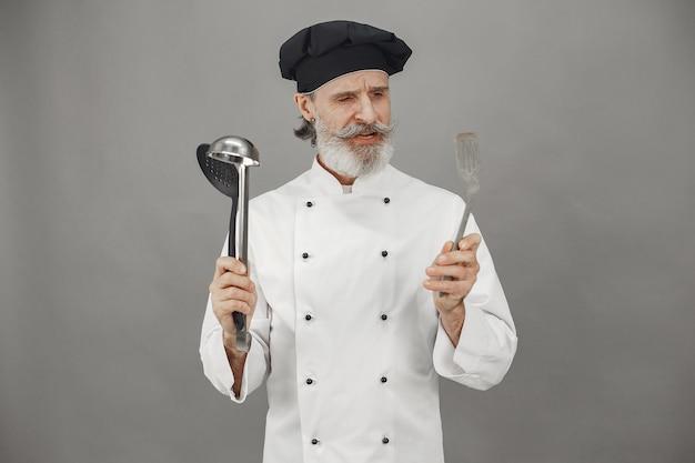 年配の男性はおたまを選びます。頭に黒い帽子をかぶったシェフ。