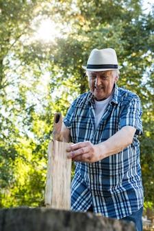 Пожилой мужчина рубит дрова
