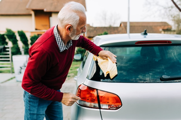 Senior man cleaning car with rag, car detailing (or valeting) concept.
