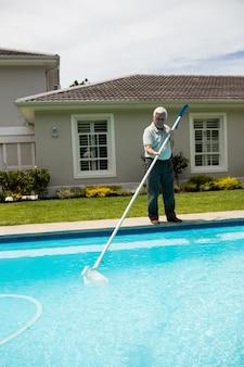 Старший мужчина чистит бассейн в солнечный день